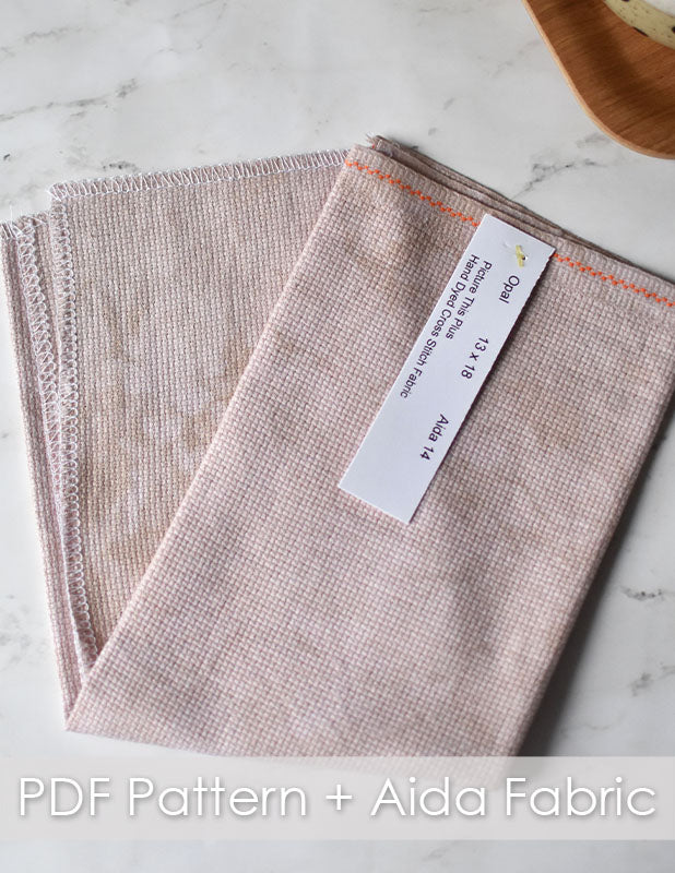 Cozy cafe club aida fabric. Neutral fabric folded in half on a marble counter top.