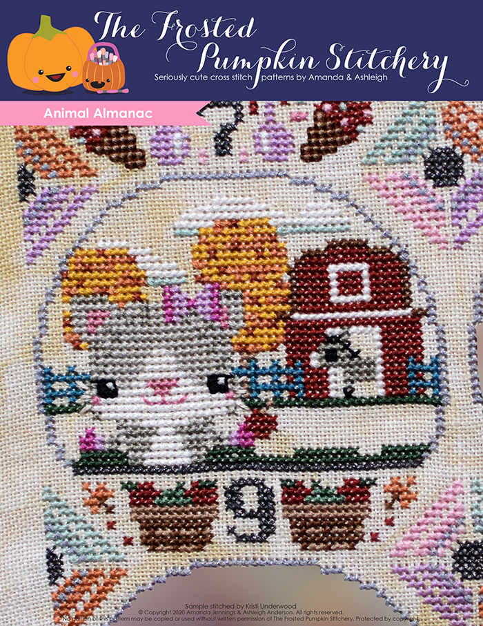 Animal Almanac Cross Stitch Pattern Cover. Image of cat wearing a bow and mittens holding an apple in front of a barn. The barn is surrounded by fall colored trees and inside the barn is a donkey.