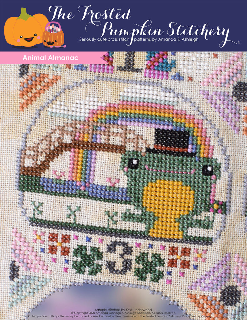 Animal Almanac Cross Stitch Pattern Cover. Image of a frog who is wearing a top hat in front of a bridge with a rainbow.