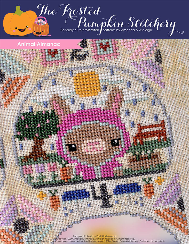 Animal Almanac Cross Stitch Pattern Cover. Image of a bunny in a raincoat holding a carrot. It is raining, the sun is trying to come out and there are plants and a garden in the background.