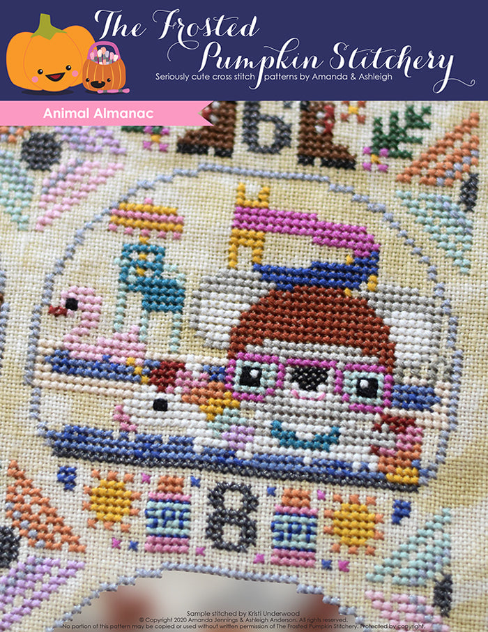 Animal Almanac Cross Stitch Pattern Cover. Koala wearing swim cap, goggles and floating in pool at waterpark wearing a unicorn floaty. Lifeguard stand and swan floaty in background.