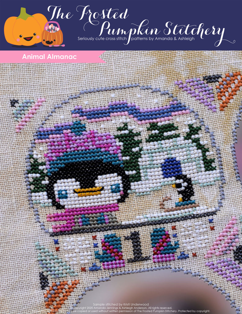 Animal Almanac Cross Stitch Pattern Cover. Image of a penguin dressed in a knit hat in front of an igloo. The Aurora Borealis is in the background.