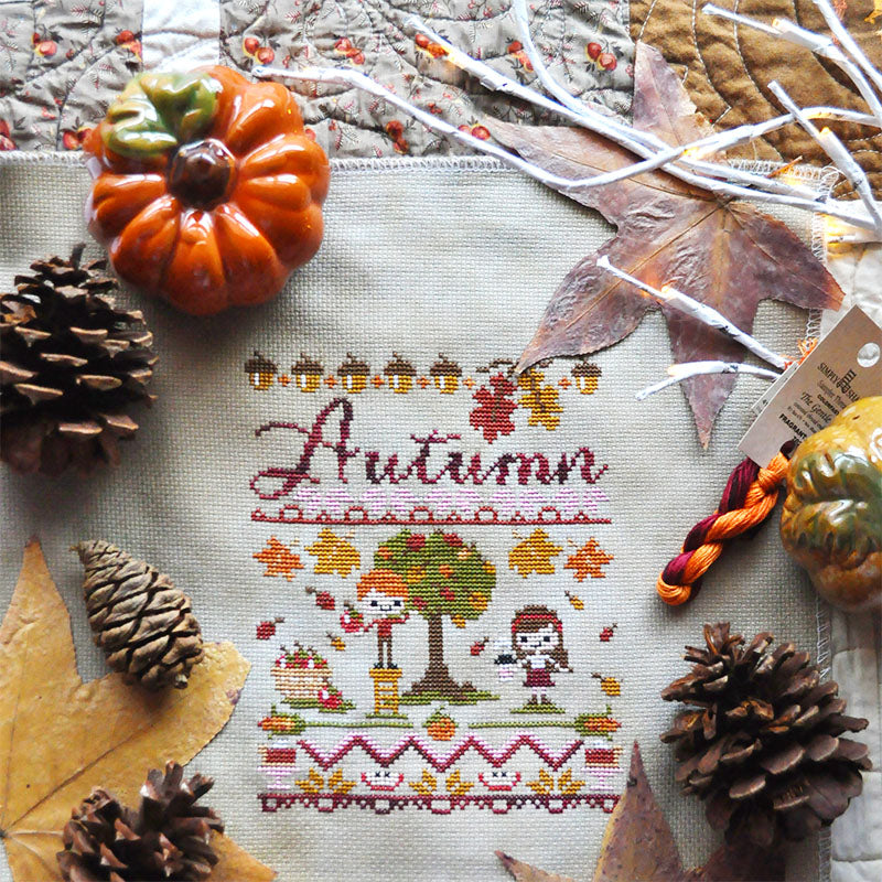 Flat lay image of Autumn Harvest Festival counted cross stitch pattern on a quilt with pine cones, leaves, a ceramic pumpkin.