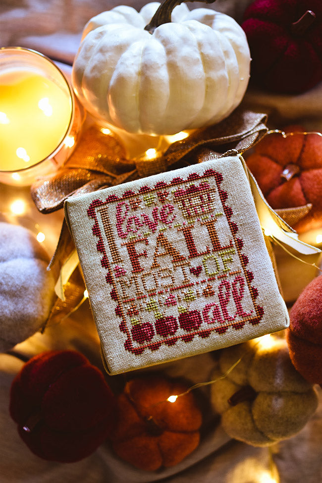 "I love Fall counted cross stitch pattern. Text reads ""I love fall most of all"" in variegated embroidery floss with a basket of apples and surrounded by apples and felt pumpkins."