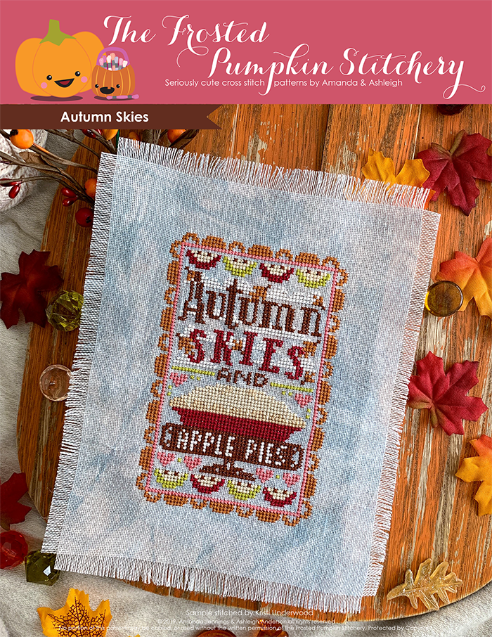 Autumn Skies counted cross stitch pattern. Text reads Autumn Skies and Apple Pies. Image of blue linen with the pattern cross stitched onto it, a big apple pie in the center, pie slices on the borders.