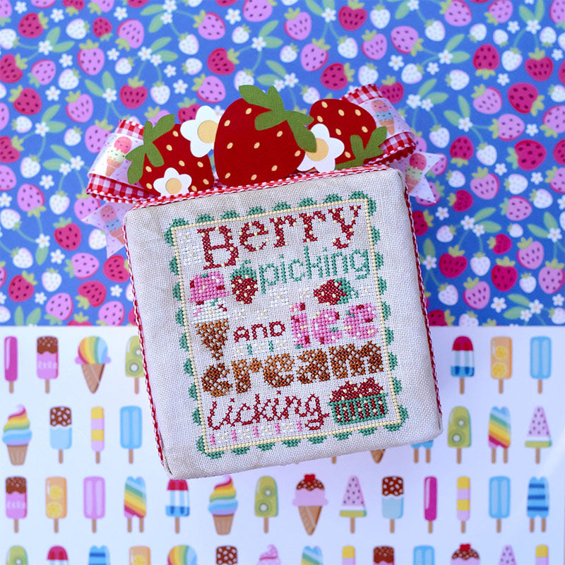 "Berry Picking counted cross stitch pattern. Text reads ""Berry Picking and Ice Cream Licking"". The font looks like ice cream with sprinkles and waffle cone. Background of the image is half popsicles and half strawberries"