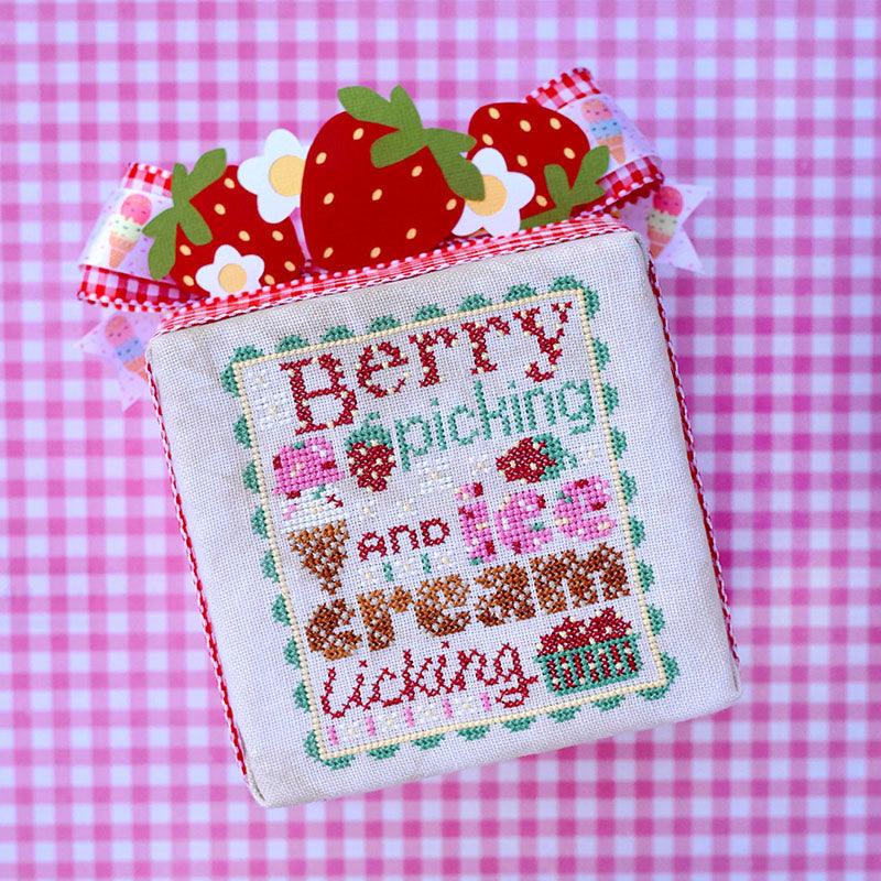 "Berry Picking counted cross stitch pattern. Text reads ""Berry Picking and Ice Cream Licking"". The font looks like ice cream with sprinkles and waffle cone. Background is pink gingham."