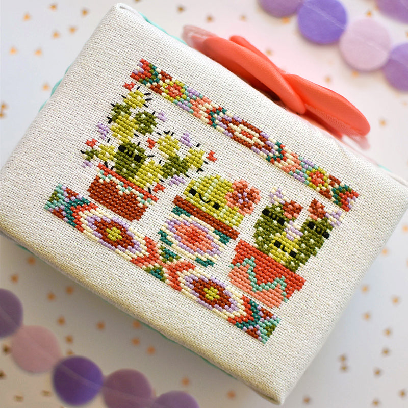 Flat lay of cactus party counted cross stitch pattern with a purple polka dot background