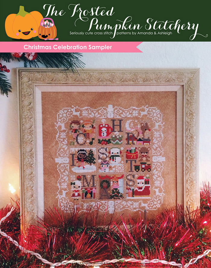 Christmas Celebration Sampler counted cross stitch pattern. Stitched on neutral fabric in a gold frame surrounded by red and green tinsel.