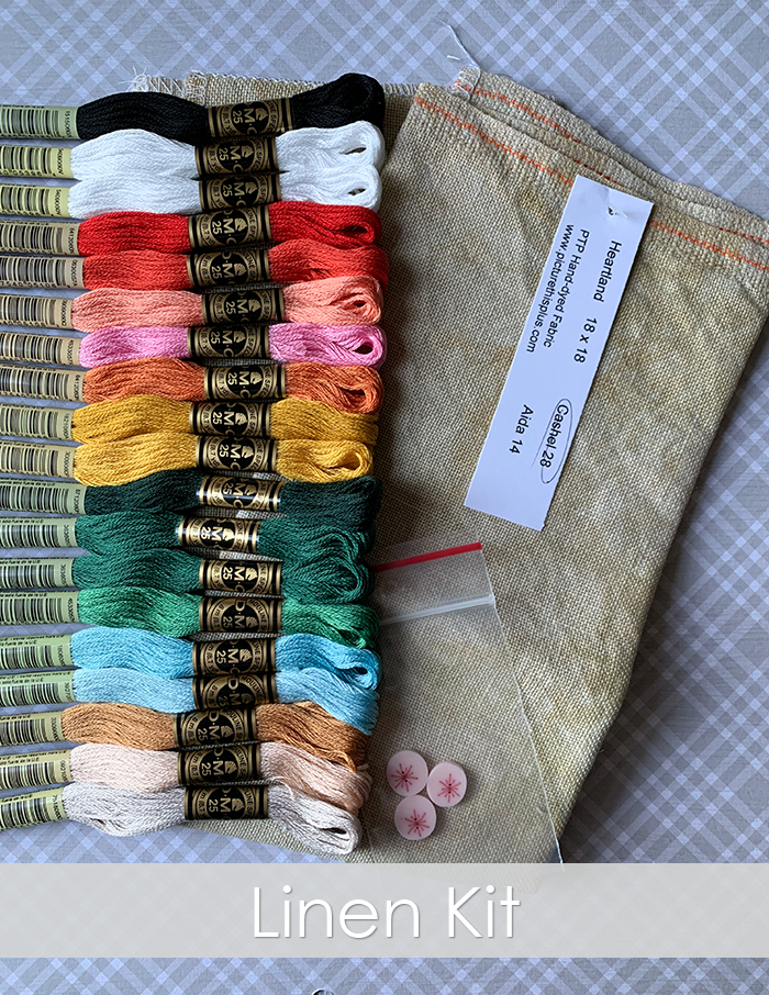 Photo of a linen kit from The Frosted Pumpkin Stitchery. Neutral linen in the color Heartland is laid on top of gray plaid paper with a rainbow of DMC threads, buttons from Just Another Button Company.