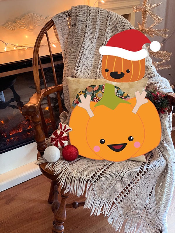 Sugarloaf the Pumpkin is dressed as a reindeer and he's sitting on a chair with a knit afghan. Jack the Pumpkin is wearing a Santa hat and is perched on the Christmas Wreath sample pillow. The background is a fireplace and a silver tinsel tree.