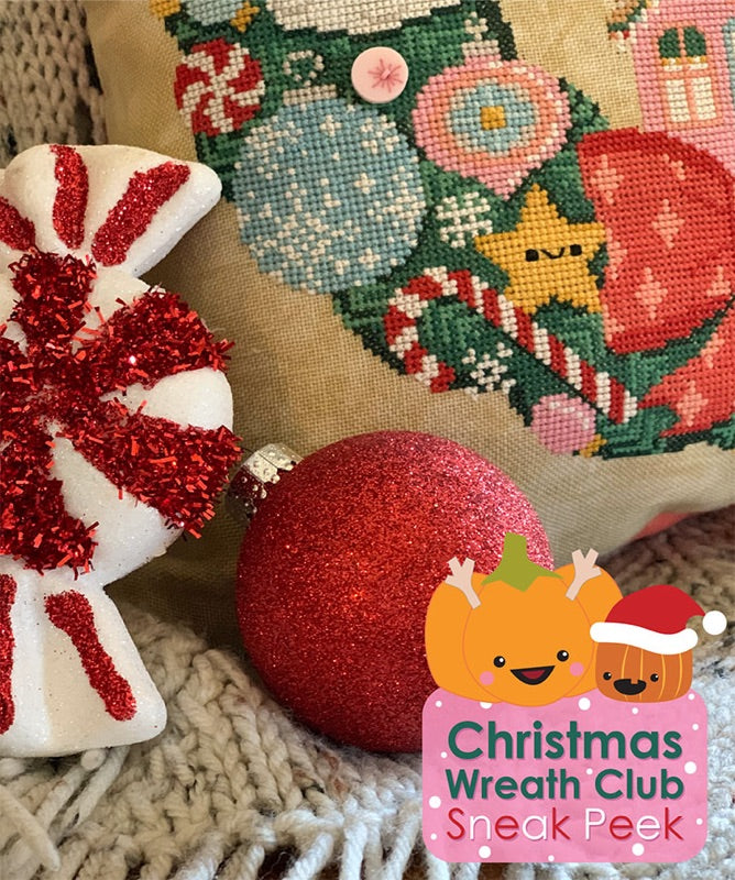 Christmas Wreath Club Sneak Peek. Two Christmas ornaments are balanced next to the corner of the pillow. The pillow is cross stitched with candy canes, a bow and ornaments.