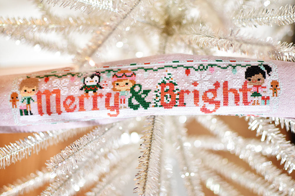 Merry and Bright counted cross stitch pattern. Three friends are decorating for the holidays with some penguins. Finished cross stitch piece is laying across branches of a tinsel tree.