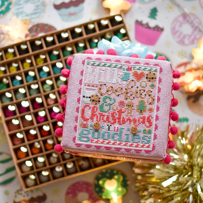Counted cross stitch pattern. Text reads Milk, Cookies and Christmas Goodies. A finished cross stitch pattern on a foam cube is laying on a box of ornaments.