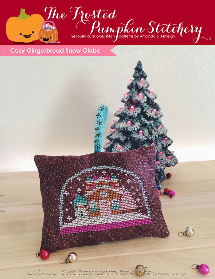 Cozy Gingerbread Snow Globe counted cross stitch pattern. A snowglobe with a snowman, gingerbread house and pink tree.