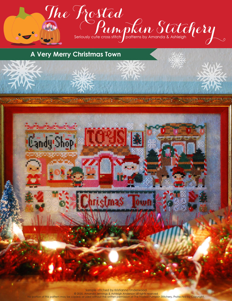 A Very Merry Christmas Town counted cross stitch pattern with a candy shop, Mrs. Claus, toy shop, Santa, reindeer and a Christmas tree lot.