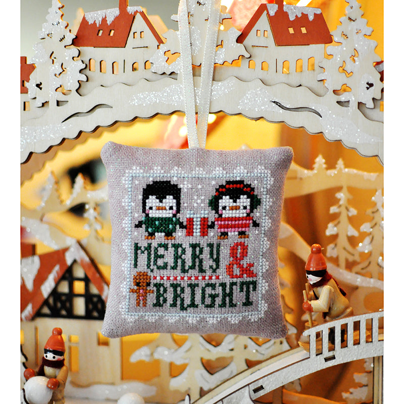 Penguin Merry and Bright Christmas ornament is hanging from a laser cut wooden scene.