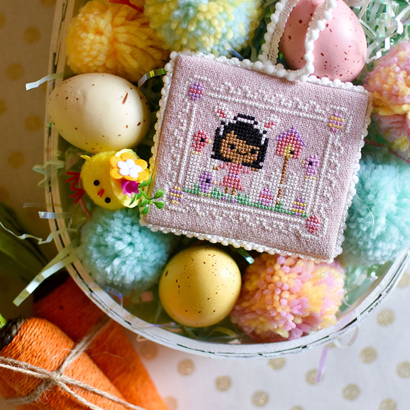 Easter Egg Hunt Counted Cross Stitch Pattern. A dark skinned girl with black hair is wearing bunny ears and Easter egg hunting with some small chicks. It's finished as a flat fold and there are pom poms in a basket.