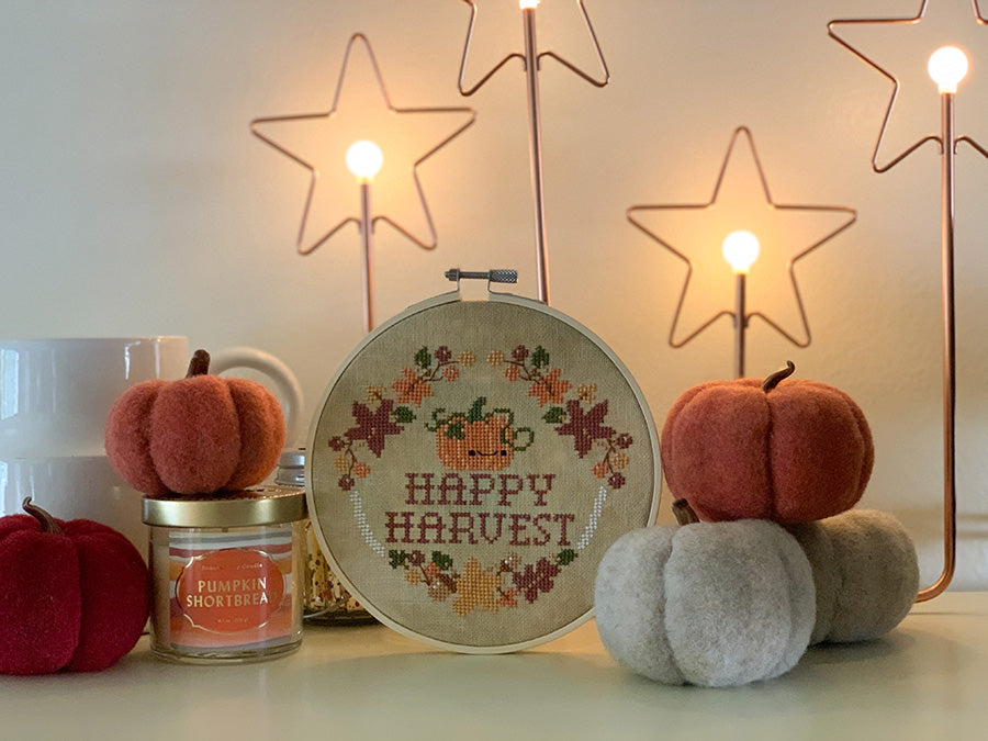Happy Harvest cross stitch pattern. Design is a pumpkin with a face, surrounded by leaves and acorns. It's in an embroidery hoop surrounded by felt pumpkins, a candle and some glow-y star lights.