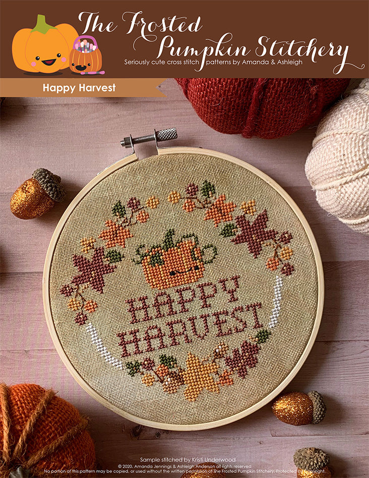 "Happy Harvest cross stitch cover image. Picture of a pumpkin surrounded by autumn leaves, acorns, berries and the words ""Happy Harvest."""