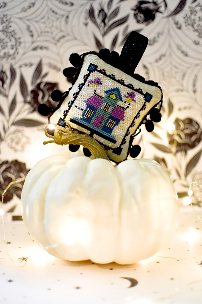 Haunted Birdhouse Halloween counted cross stitch pattern. Ornament placed on top of a white pumpkin.