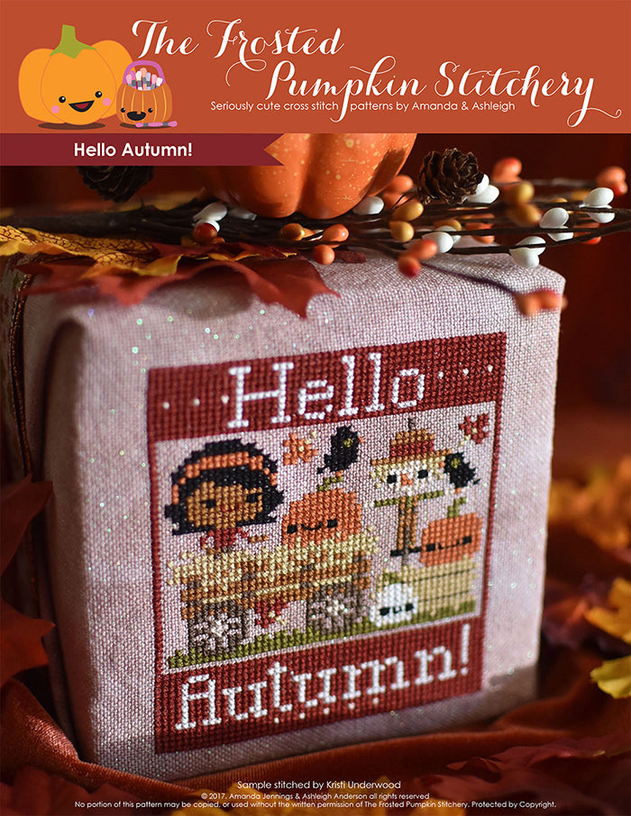 Hello Autumn counted cross stitch pattern. Brown skinned girl is on a hay ride with pumpkins and a scarecrow.