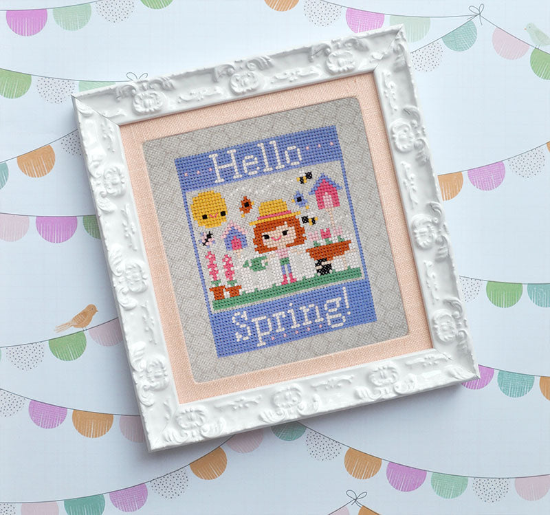 "Hello Spring counted cross stitch pattern. A white girl with red hair is gardening. Text reads ""Hello Spring"". It's framed in a white frame with peach molding."