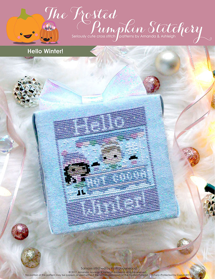 "Hello Winter counted cross stitch pattern. A brown skinned girl with long dark hair is having hot cocoa with a white skinned boy with short light brown hair at a hot cocoa stand. Text reads ""Hello Winter""."