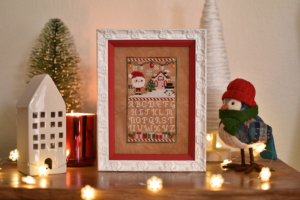 Holly Jolly Sampler counted cross stitch pattern. Christmas pattern with santa, a snowman and a little house above the alphabet. Surrounded by a ceramic house, a fake bird wearing a hat and a bristle tree.