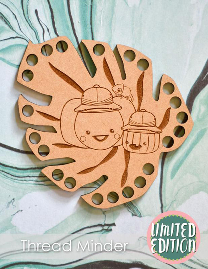 Wooden thread minder in the shape of a leaf with two pumpkins dressed in safari hats.