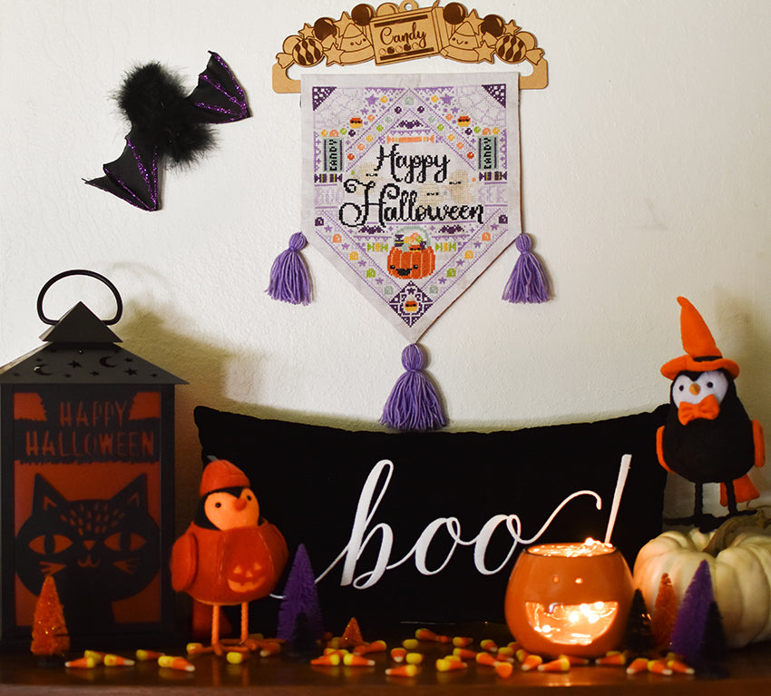 "Jack's Halloween Dream counted cross stitch pattern hanging in our home. Pillow with text that says ""boo"" on a pillow, a lantern that says ""happy halloween"" and candy corn."