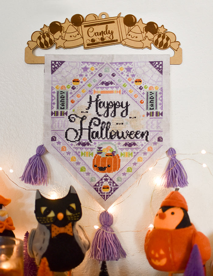 "Jacks Halloween Dream counted cross stitch pattern. A hanging banner on a white wall surrounded by twinkle lights and a black and orange birds. Text reads ""Happy Halloween""."