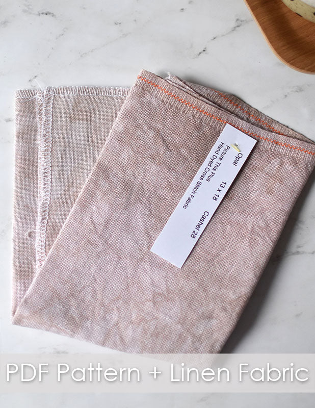 Cozy cafe club linen fabric. A neutral colored linen folded in half on a marble countertop.
