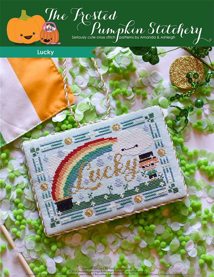 Lucky counted cross stitch pattern. Finished as a flat fold with gold and white trim. Pattern is a rainbow with a pot of gold, a cloud with a face, a leprechaun and grass.