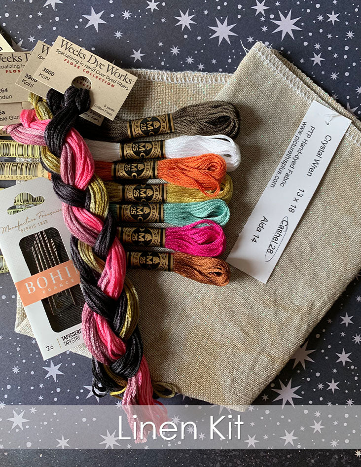 Mysterious Halloween Town linen kit. Skeins of embroidery floss on neutral colored linen fabric on a black starry background.