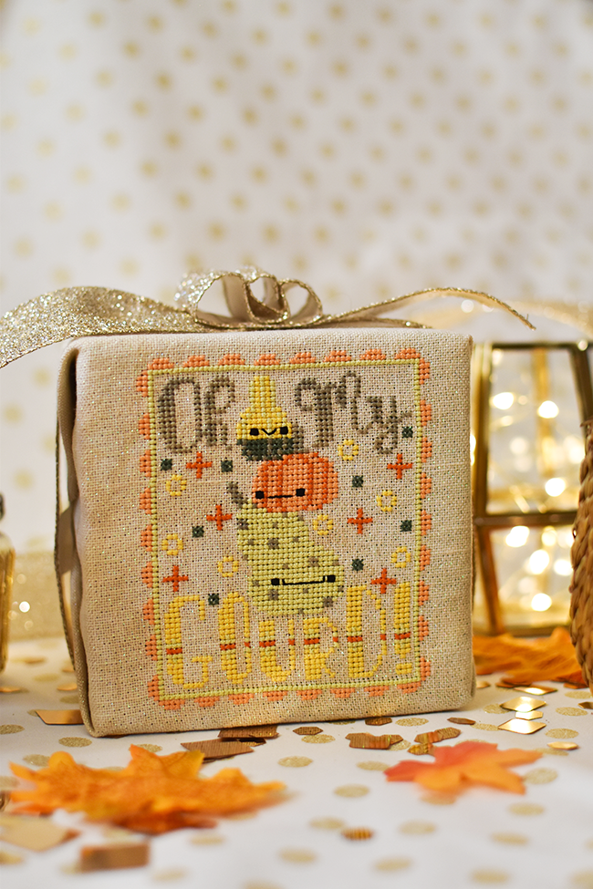 "Oh My Gourd counted cross stitch pattern with a stack of three gourds all with faces. The text around them reads ""oh my gourd""."