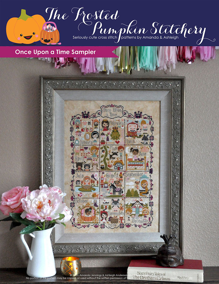 Once Upon a Time Sampler counted cross stitch pattern. Stories include Snow White, Frog Prince, Three Little Pigs and more. Framed piece is against a neutral wall with peonies in a vase in front of it.