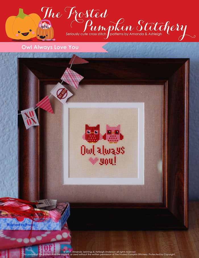 "Owl Always Love You counted cross stitch pattern. Two little owls, one pink and one red are sitting next to each other. Text reads ""Owl Always Love You"". Owls are stitched on perforated paper and in a brown frame."