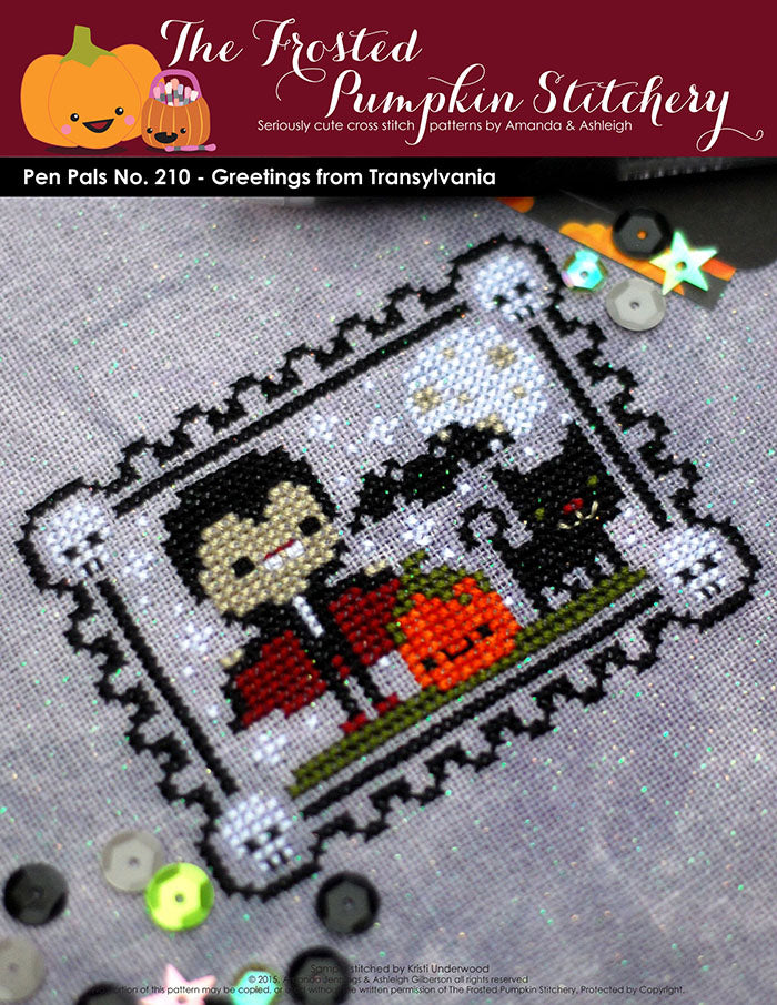 Pen Pals No 210 Halloween Greetings from Transylvania counted cross stitch pattern. Dracula stands next to a pumpkin and a black cat.