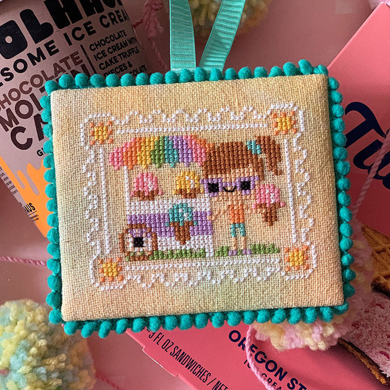 Pen Pals No 207 Ice Cream You Scream counted cross stitch pattern.  A little girl with big purple sunglasses holds an ice cream cone next to an ice cream cart.