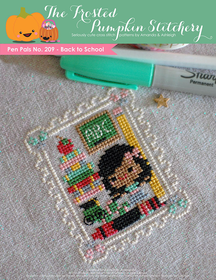Pen Pals No 209 Back to School counted cross stitch pattern. A girl with brown skin and dark hair stands with a caterpillar wearing glasses and a chalk board that says ABC.