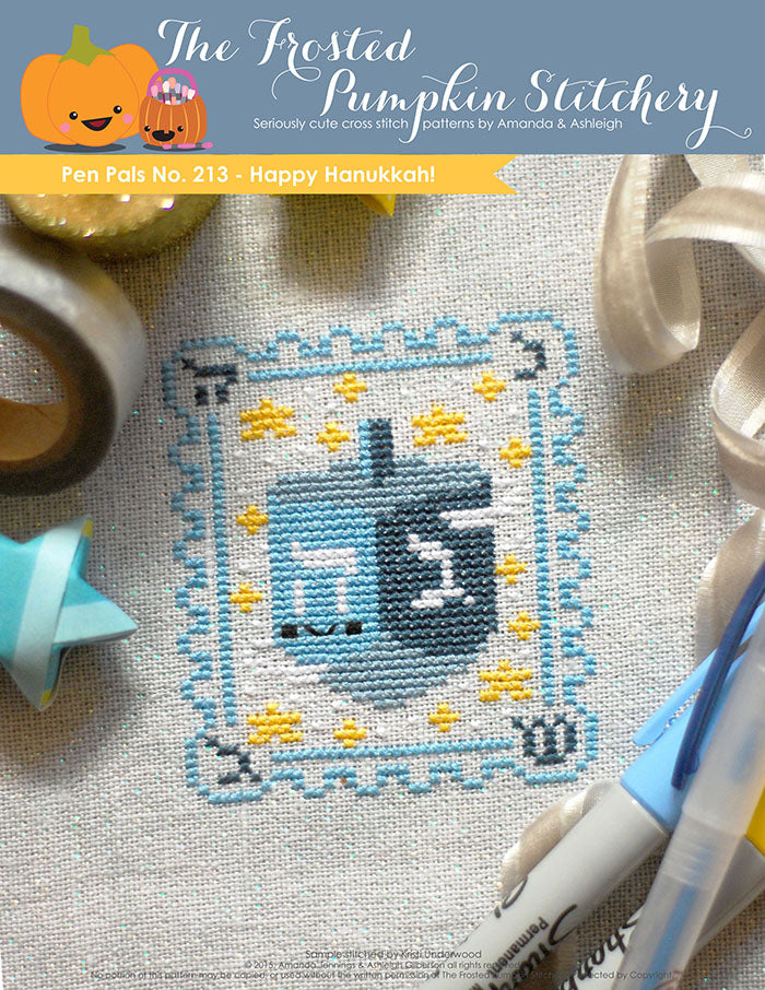 Pen Pals No 213 Happy Hannukah counted cross stitch pattern. A blue dreidel with a kawaii face surrounded by stars.