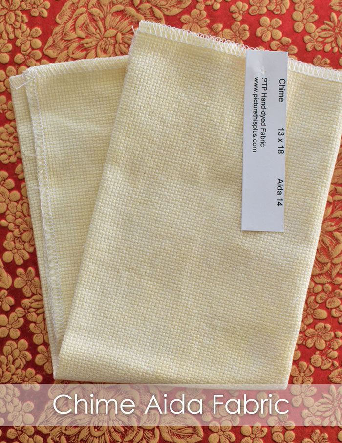 Picture This Plus Chime Aida Fabric. A pale yellow piece of fabric is folded in half on a red and gold brocade background.