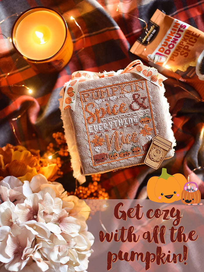 "Pumpkin Spice and Everything Nice counted cross stitch pattern cozy flat lay. Cross stitch pattern is laying on a plaid blanket surrounded by candles and a bag of pumpkin spice coffee. Text reads ""get cozy with all the pumpkin""."