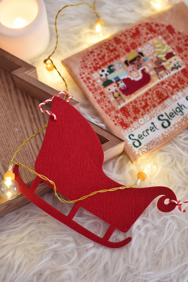 A felt sled on a fake sheep skin rug with candles and Secret Sleigh Society in the background.
