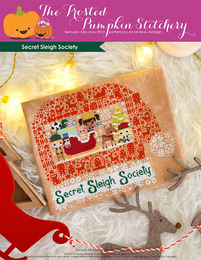 "Secret Sleigh Society counted cross stitch pattern. Three elves surround Santa's sleigh with the text below ""Secret Sleigh Society""."