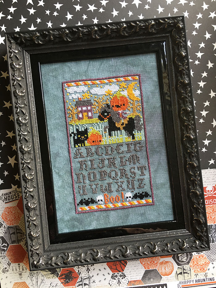 Sleepy Hollow Sampler counted cross stitch pattern. The headless horsemen is riding in the village at night. Alphabet below in a Halloween inspired font. Framed in a gothic thick black frame.