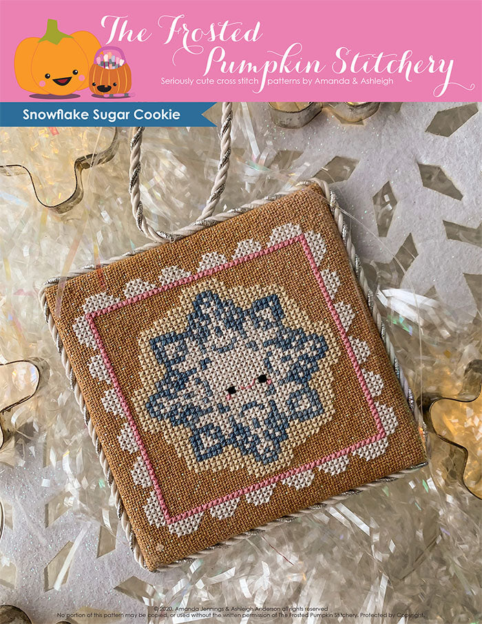 Image of Snowflake Sugar Cookie Cross Stitch Pattern. This pattern features a  snowflake shaped sugar cookie, surrounded by a pink and white frosting frame.