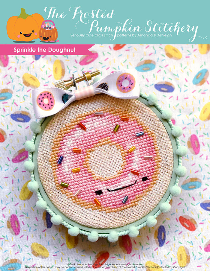 Sprinkle the Doughnut counted cross stitch pattern. Sprinkle is a doughnut with pink frosting and bead sprinkles. He's finished in a mint green embroidery hoop.