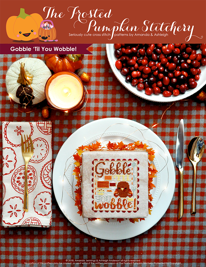 "Gobble 'Til You Wobble Thanksgiving counted cross stitch pattern. A finished cross stitch pattern in a plate with place settings and cranberries. Text reads ""Gobble Til You Wobble"""